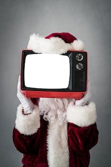 Weihnachtsmann, der retro-fernseher mit leerem weihnachtsweihnachtsfeiertagskonzept hält