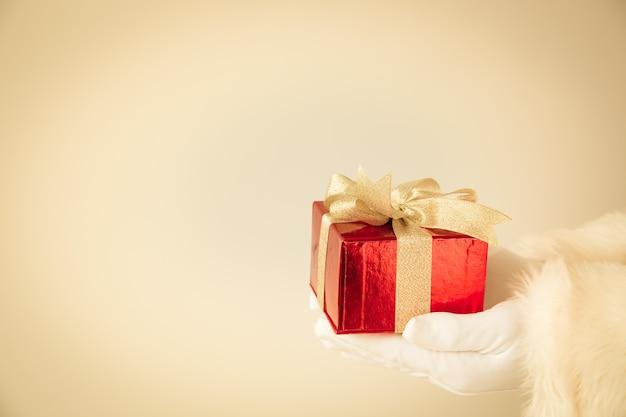 Weihnachtsmann, der rote geschenkbox in den händen hält. weihnachtsferienkonzept