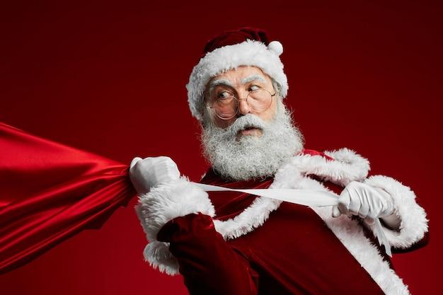 Weihnachtsmann, der sack mit weihnachtsgeschenken hält