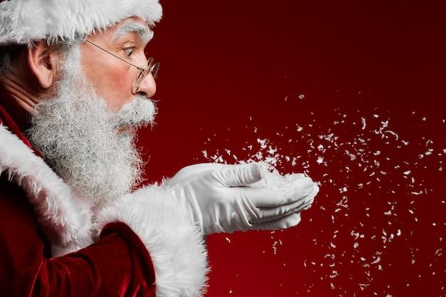Weihnachtsmann, der schnee auf rot bläst