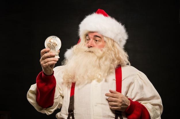 Weihnachtsmann, der schnekugel hält