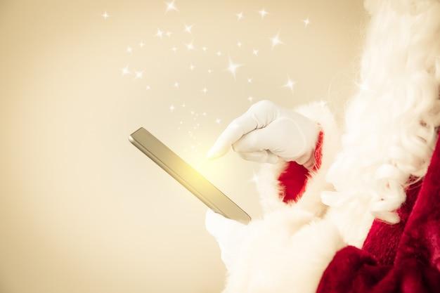 Weihnachtsmann, der tablet-pc in den händen hält. weihnachtsferienkonzept