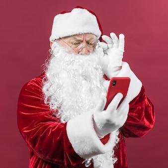Weihnachtsmann, der telefonschirm betrachtet