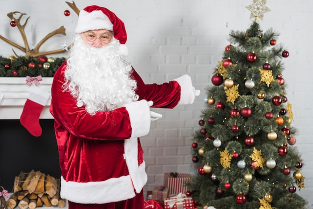 Weihnachtsmann, der weihnachtsbaum mit den händen zeigt
