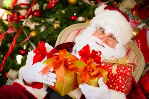 Weihnachtsmann, der weihnachtsgeschenk hält. weihnachtsferienkonzept