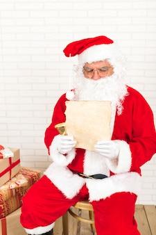 Weihnachtsmann, der weinlesepapier sitzt und liest