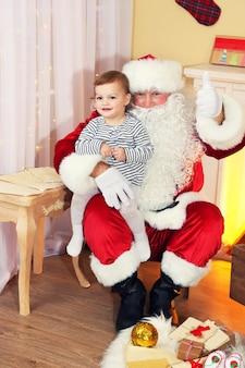 Weihnachtsmann, der zu hause ein kleines süßes mädchen in der nähe von kamin und weihnachtsbaum hält