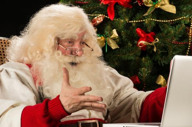 Weihnachtsmann, der zu hause laptop gegen weihnachtsbaum verwendet und ist wirklich beeindruckt