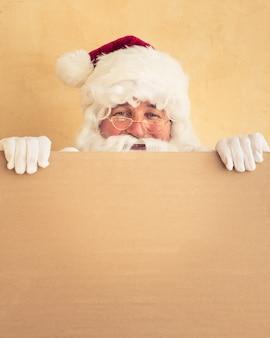 Weihnachtsmann hält banner leer. weihnachtsferienkonzept