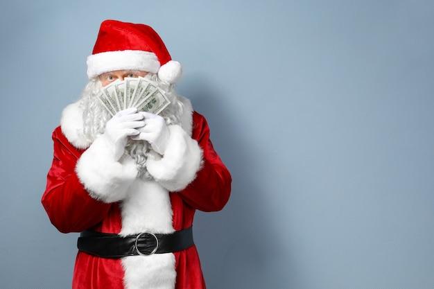 Weihnachtsmann hält geld auf hellem hintergrund