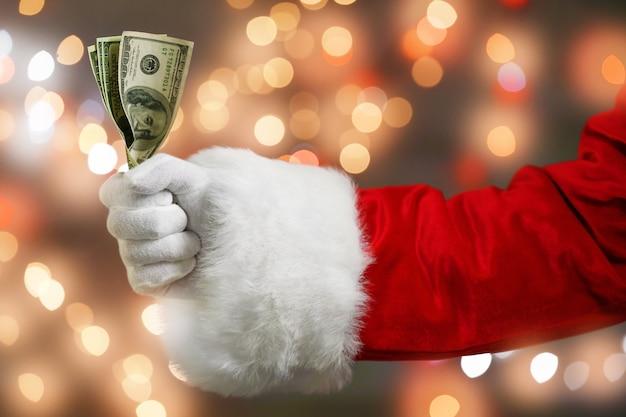Weihnachtsmann hält geld gegen defokussierte lichter