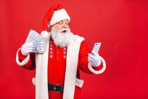 Weihnachtsmann hält geld und benutzt telefon