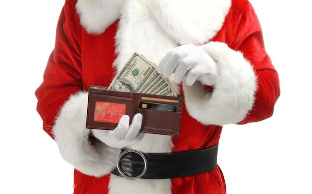 Weihnachtsmann hält geldbörse mit geld an weißer wand