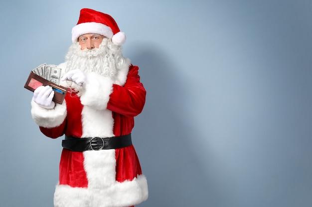Weihnachtsmann hält geldbörse mit geld