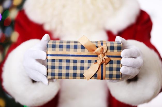 Weihnachtsmann hält geschenk auf weihnachtsbaumoberfläche