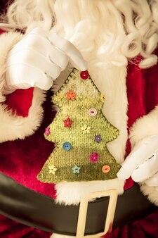 Weihnachtsmann hält gestrickten weihnachtsbaum in händen. weihnachtsferienkonzept