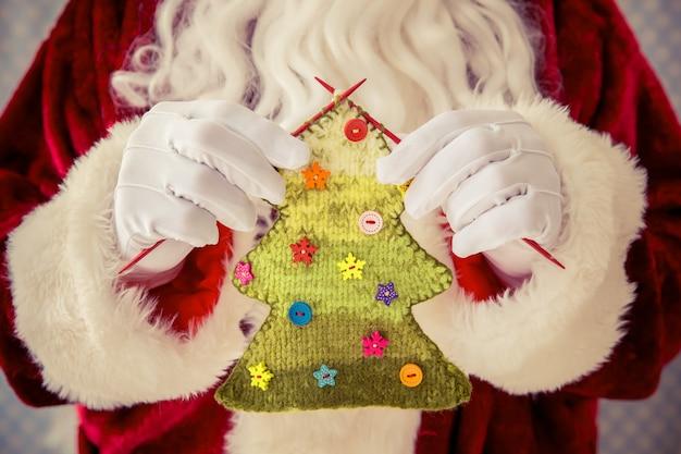 Weihnachtsmann hält gestrickten weihnachtsbaum in händen