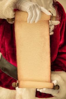 Weihnachtsmann hält rollenpapier leer in den händen. weihnachtsferienkonzept