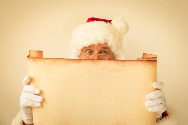 Weihnachtsmann hält rollenpapier leer. weihnachtsferienkonzept