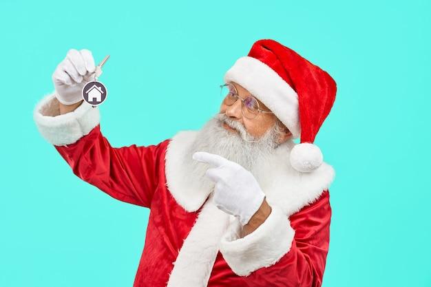 Weihnachtsmann hält schlüssel mit hausschild.