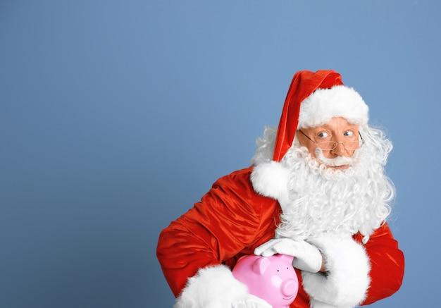 Weihnachtsmann hält sparschwein auf blauem hintergrund