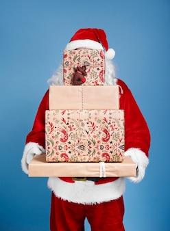 Weihnachtsmann hält stapel von weihnachtsgeschenken