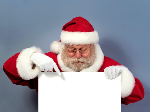 Weihnachtsmann hält weiße tafel und zeigt darauf.