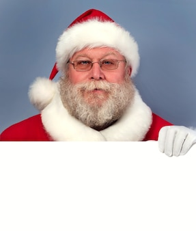 Weihnachtsmann hält weiße tafel.