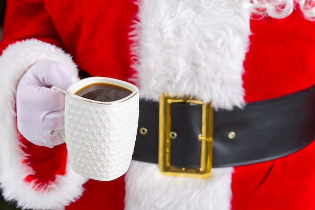Weihnachtsmann hält weiße tasse mit kaffee in der hand nahaufnahme