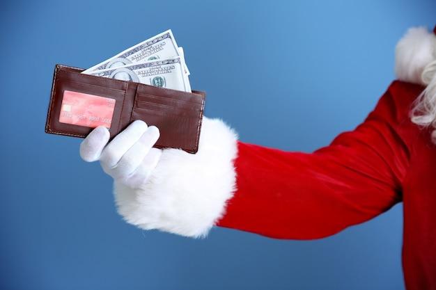 Weihnachtsmann-hand, die geldbörse mit geld und kreditkarte auf blauem hintergrund hält