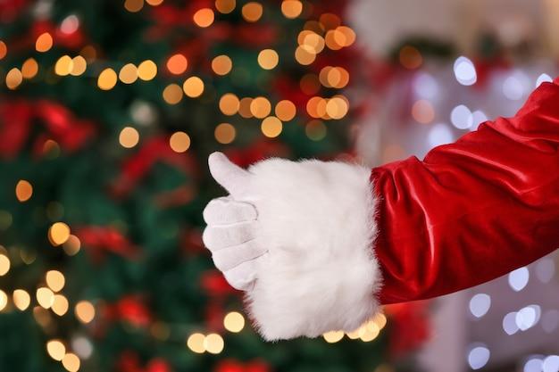 Weihnachtsmann-hand gegen verschwommene weihnachtsbeleuchtung
