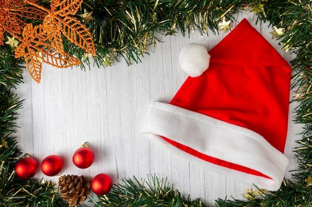 Weihnachtsmann-hut mit weihnachtsschmuck auf holztisch.