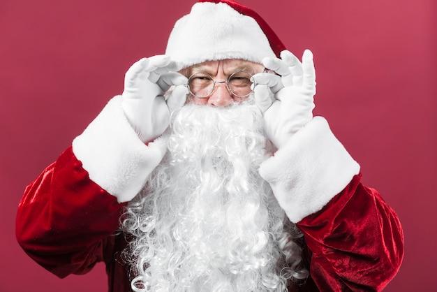 Weihnachtsmann im hut, der auf rotem hintergrund lugt