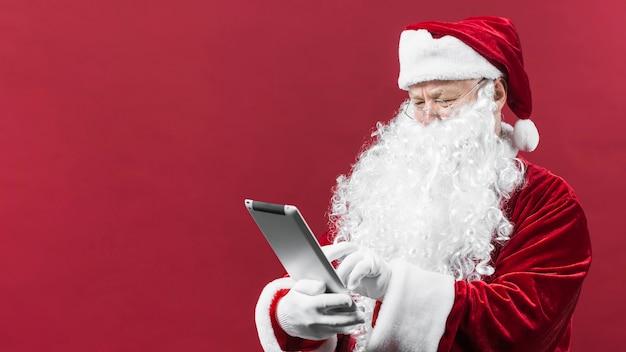 Weihnachtsmann im hut unter verwendung der tablette