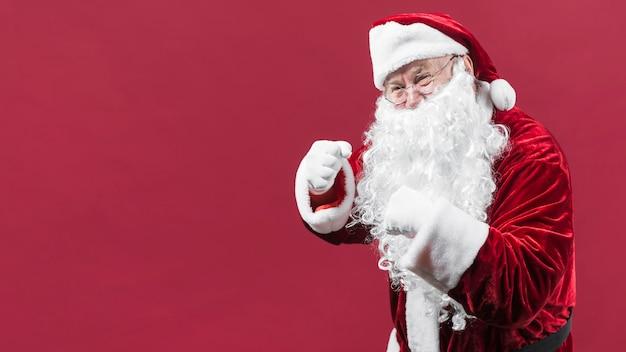 Weihnachtsmann im roten hut, der fäuste zeigt