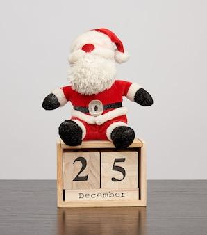 Weihnachtsmann im roten hut, hölzerner kalender der tabelle mit dem datum am 25. dezember