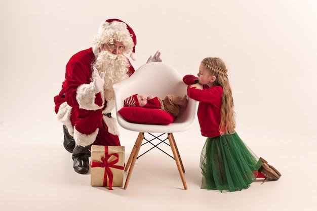 Weihnachtsmann im roten kostüm mit einem kleinen mädchen und einem baby lokalisiert auf weiß