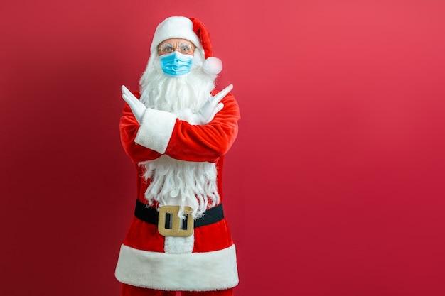 Weihnachtsmann in einer medizinischen maske auf einem roten hintergrund.