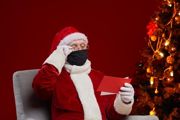 Weihnachtsmann in schutzmaske und in brille liest wunschbriefe von kindern