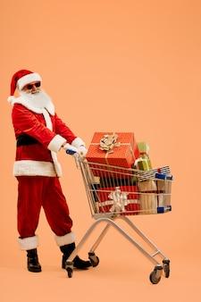 Weihnachtsmann in sonnenbrille mit wagen mit geschenken gefüllt