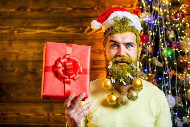 Weihnachtsmann in weihnachtsmütze halten weihnachtsgeschenk frohe weihnachten und ein gutes neues jahr weihnachtsleute cel ...