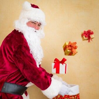 Weihnachtsmann jongliert weihnachtsgeschenkboxen. weihnachtsferienkonzept