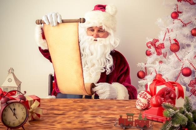 Weihnachtsmann liest schriftrolle. weihnachtsferienkonzept
