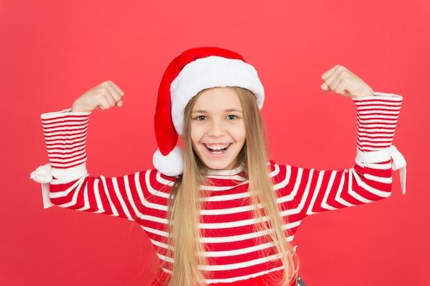 Weihnachtsmann macht. glückliches kind in den flexarmen des sankt-kostüms. kleines mädchen mit santa-look zeigt stärke. lieber weihnachtsmann, ich war stark. weihnachten und neujahr.