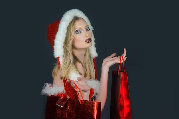 Weihnachtsmann-mädchen in santa-helfer-hut mit einkaufstasche in den händen. konzept des neuen jahres und der frohen weihnachten.