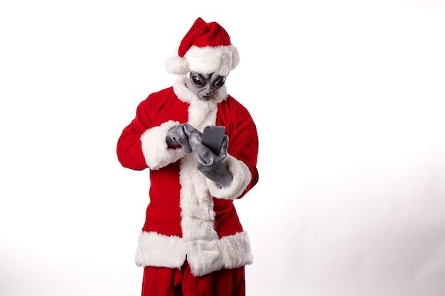 Weihnachtsmann mit alien-maske trägt ein smartphone auf weißem hintergrund