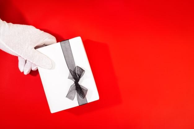 Weihnachtsmann mit behandschuhten händen, die ein weihnachtsgeschenk halten.
