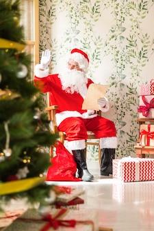 Weihnachtsmann mit dem buchstaben, der auf stuhl sitzt