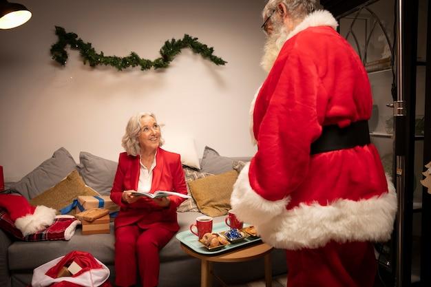 Weihnachtsmann mit der älteren frau betriebsbereit zu weihnachten