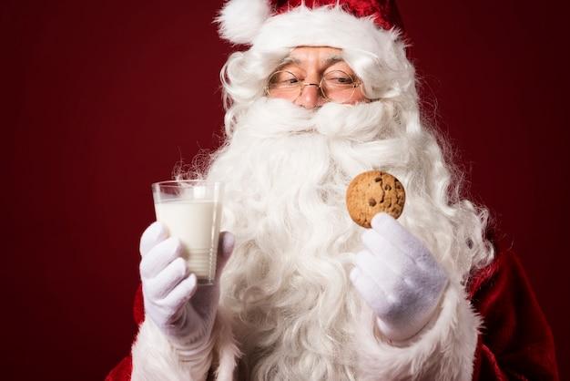 Weihnachtsmann mit einem keks und einem milchglas